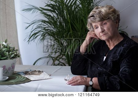 Eldery woman is sitting alone