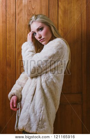 Young beautiful blonde sexy girl in wool coat and colorful pants standing in front of old locker