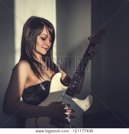 Portrait of a beautiful young woman with an electric guitar