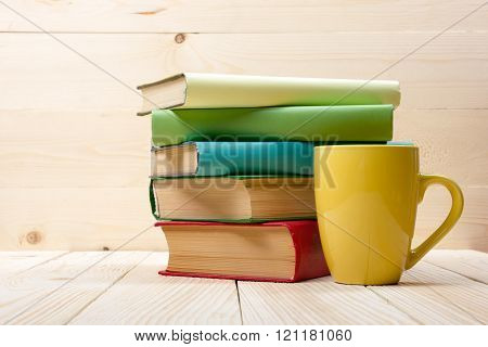 Stack of colorful books and cup on wooden table. Back to school. Copy space
