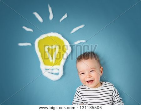 One year old boy and a bulb near. Child with an idea