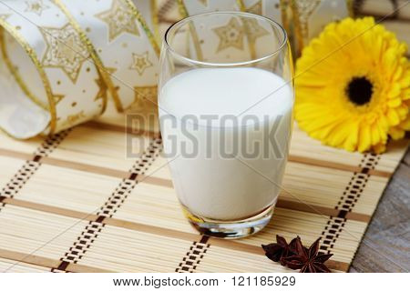 Glass of milk, gerber and anise on the wooden table
