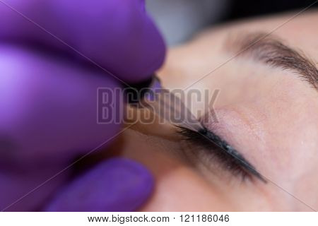 Cosmetologist applying permanent makeup on eyes