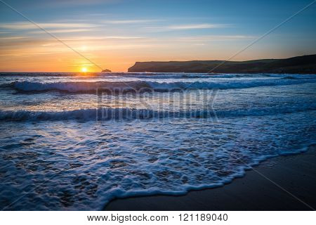 Lapping waves at sunset at Polzeath beach, Cornwall, UK