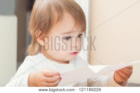 Curious Toddler Girl Reading Something