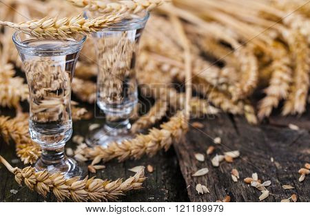 Clear liquor and cereal on old garden table ** Note: Shallow depth of field