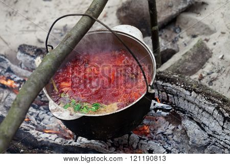 Borscht Cooking In Sooty Cauldron On Campfire