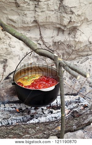 Soup Cooking In Sooty Cauldron On Campfire