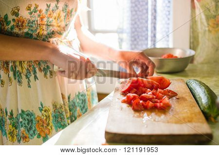 Country girl is cutting vegetables for salad in the kitchen, cooking dinner. village house, natural