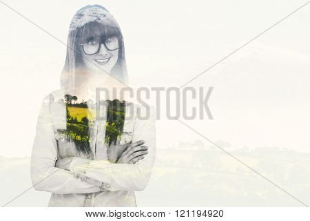Portrait of a smiling hipster woman against country scene