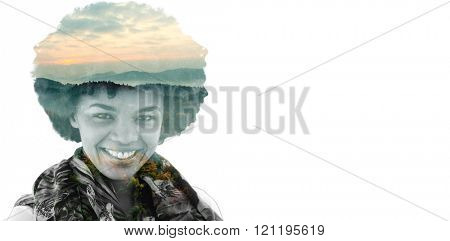Brunette smiling to the camera against trees and mountain range against cloudy sky