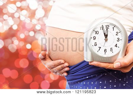 Pregnant woman showing clock and bump against glowing background