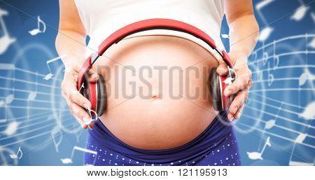 Pregnant woman holding earphones over bump against orange background