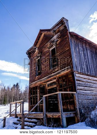 Old solitary abandoned wooden two story house in winter