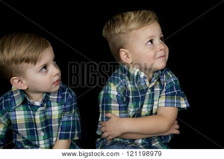 Portrait of two cute boys wearing matching shirts looking up away