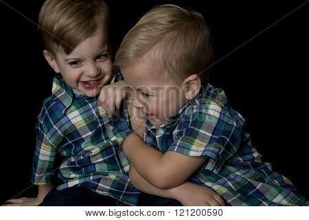 Candid Portrait Of Two Young Boys Playing Wrestling With Each Other Smiling