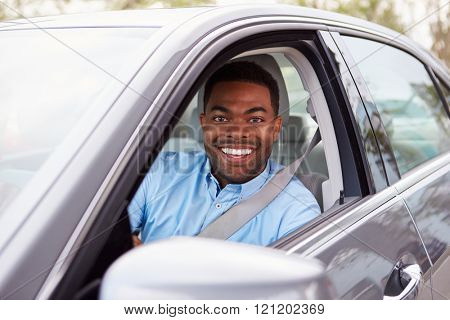 African American male driver looking to camera through car window