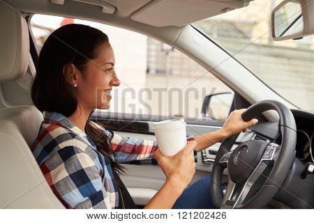 Hispanic female driver holding take away drink, in car view