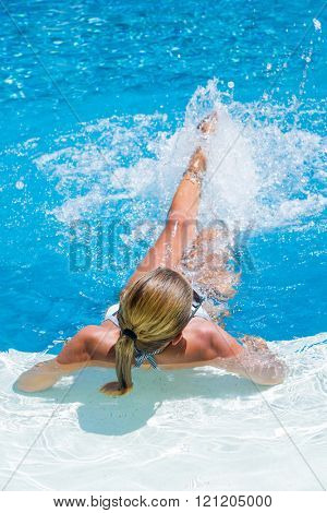 Woman at the swimming pool splashing water with her legs