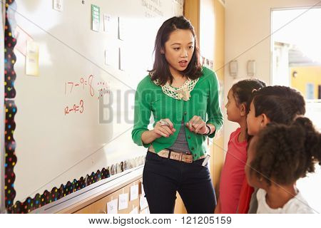 Elementary school maths class at the whiteboard with teacher