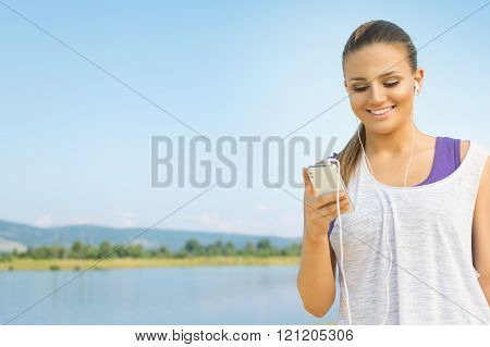Young fitness woman with smartphone and headphones