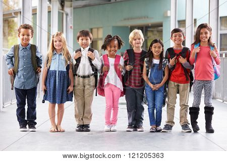 Group of elementary school kids standing in school corridor