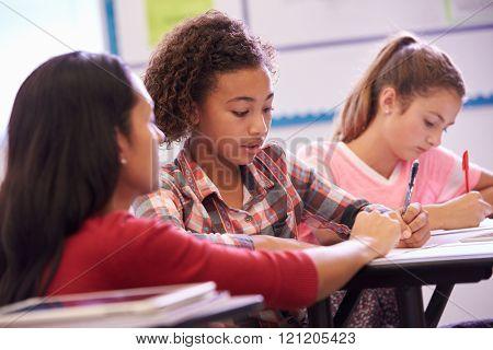 Teacher helping elementary school pupils in class
