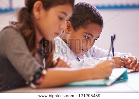 Two elementary school pupils working at desk during a lesson