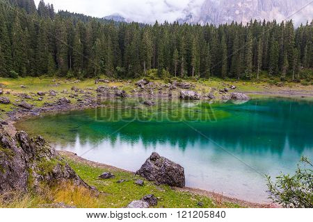 The astonishing colours of the water of the Karersee in Trentino during a rainy day