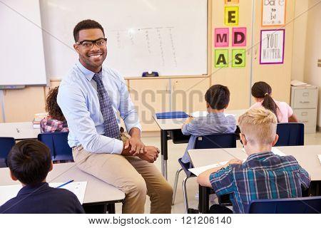 Smiling elementary school teacher sitting on a pupilâ??s desk