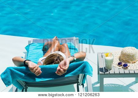 Woman relaxing at the poolside with pina colada cocktail