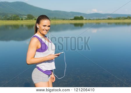 Young fitness girl with smartphone standing by the lake