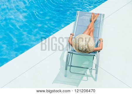 woman with hat  enjoying on sunbed at swimming pool