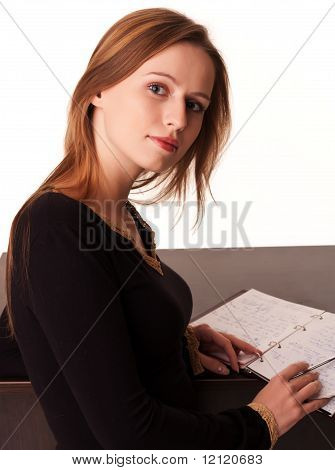 Pretty Young Girl Sitting At The Desk With Her Notebook Open