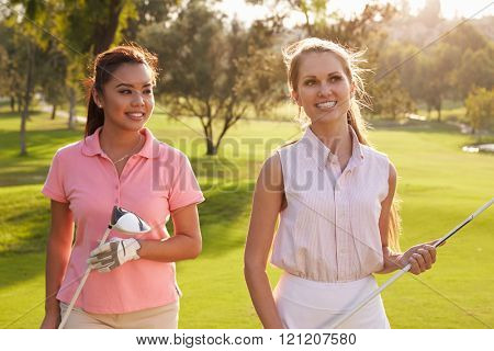 Two Female Golfers Walking Along Fairway Carrying Clubs