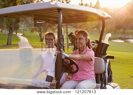 Female Golfers Driving Buggy Along Fairway Of Golf Course