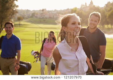 Group Of Golfers Walking Along Fairway Carrying Golf Bags