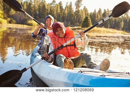 Father And Son Rowing Kayak On Lake
