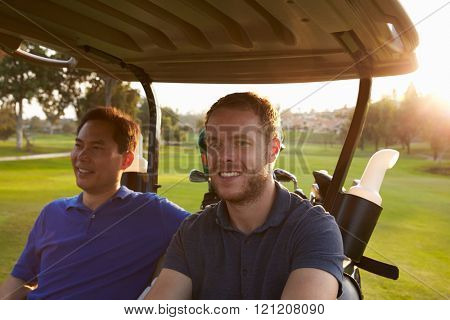Male Golfers Driving Buggy Along Fairway Of Golf Course