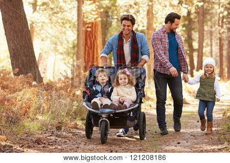 Gay Male Couple Pushing Children In Buggy Through Woods