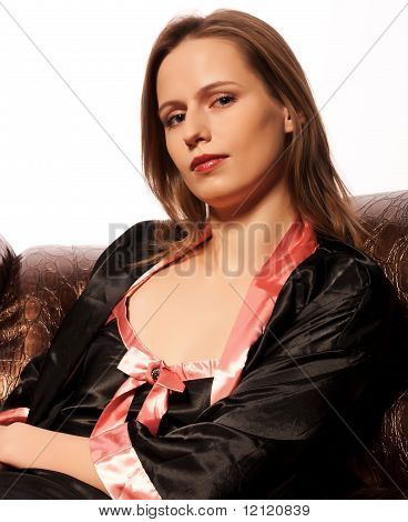 Pretty Young Woman Sitting On Leather Couch