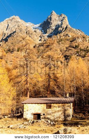 Tiny chalet in the italian Alps with a colourful panorama under a peak