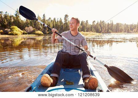 Young Man Rowing Kayak On Lake