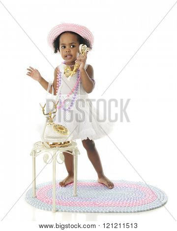 An adorable girlie girl standing in her petticoat, pearls and hat while talking on a fancy French phone.  On a white background.