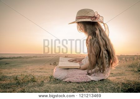 Girl reading the book on rural landscape