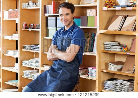 Salesman With Arms Crossed Sitting In Book Store