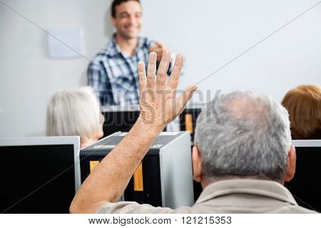 Senior Man Asking Question In Computer Class