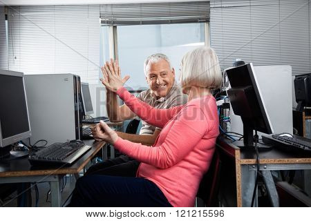 Senior People Giving High Five In Computer Class