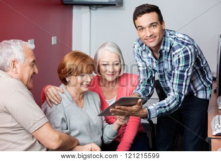 Tutor Guiding Senior Students To Use Digital Tablet In Classroom