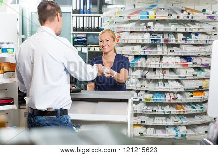 Mature Chemist Giving Product To Customer In Pharmacy